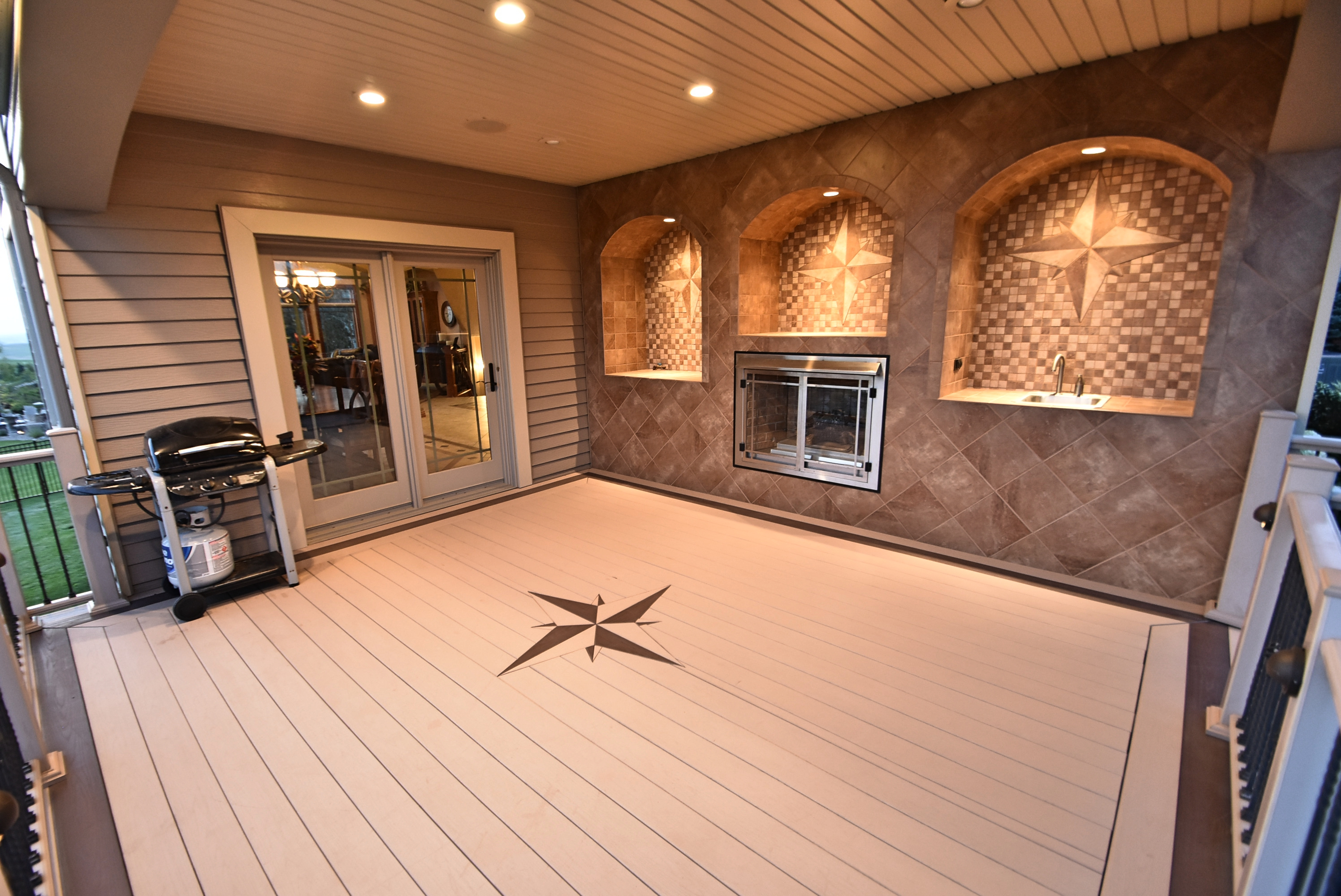 Covered deck with integrated fireplace, sink and grille area.